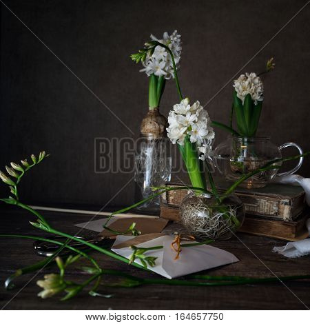 three white hyacinth and freesia in transparent vases, candle on a dark background