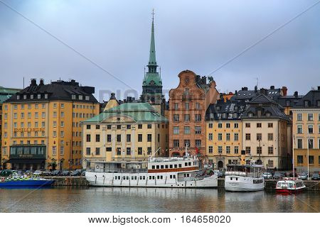 STOCKHOLM SWEDEN - AUGUST 20 2016: View of Gamla Stan from bridge Skeppsholmsbron. Old buildings on Stockholm quay and touristic sightseeing boats in Stockholm Sweden on August 20 2016.