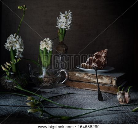 Still life with old books, cake, white hyacinths on a dark background