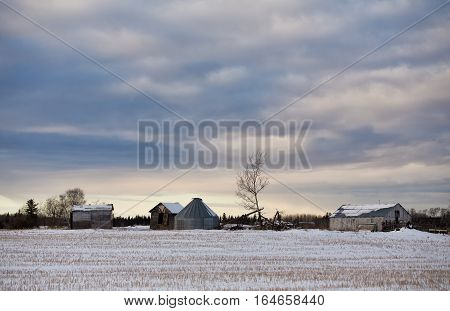 Crumbling old buildings and farm equipment beside a harvested field in a rural countryside winter landscape at dusk