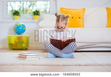 Portrait Of Clever Little Girl Sitting With Book On The Floor