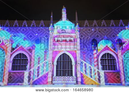An abstract image of lights being projected onto the side of a building for a holiday display on the island of macau lit up at night in Asia.