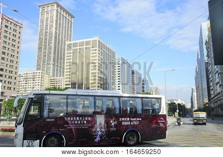 December 20, 2016. Macao, China. A tour bus on the island of macau china driving down the city streets by some apartment and office buildings.