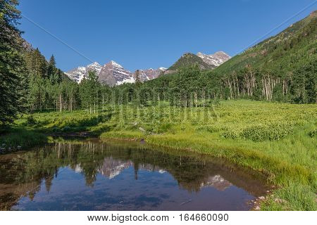 a scenic reflection of the maroon bells in a small pond in summer near Aspen Colorado