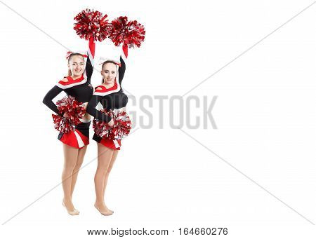 Two Professional Cheerleaders Posing At Studio. Hands Raised Up. Isolated Over White.