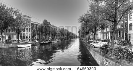 Monotone shot of typical amsterdam canal in a residential setting