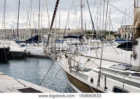 Yachts moored at Msida Marina in Malta. Sail boats in a row on docks at seaside harbor.