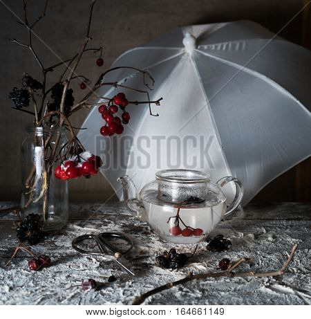 viburnum branches with berries and snow in a transparent vase, umbrella on a wooden table