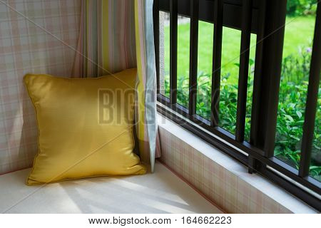 resting area of a cozy window seat with gold cushion in the morning horizontal composition