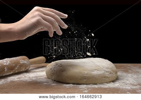 Putting some flour on a chunk of pizza dough.