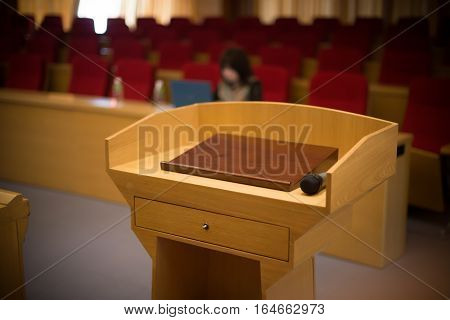 rostrum with a microphone in a reference room with one person at background