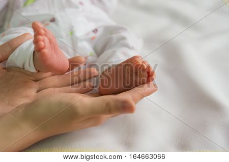 baby feet on mothers hands on white blanket