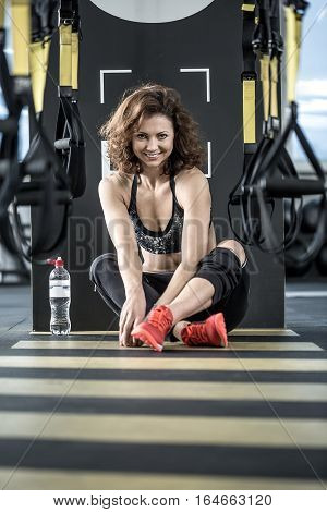 Joyful sportive woman with curly hair sits on the floor in the gym on the background of the partition. She wears dark sportswear with red sneakers. Vertical.