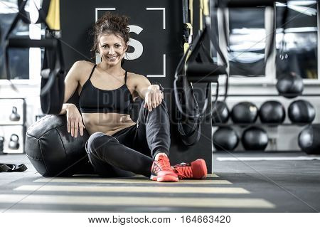 Joyous sportive woman with curly hair sits on the floor in the gym on the background of the partition. She wears dark sportswear with red sneakers. Girl leans on the black ball and smiling.