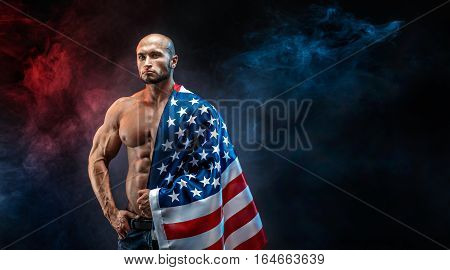Sexy shredded man with American flag on shoulder looking at camera seriously.Smoke lighted background