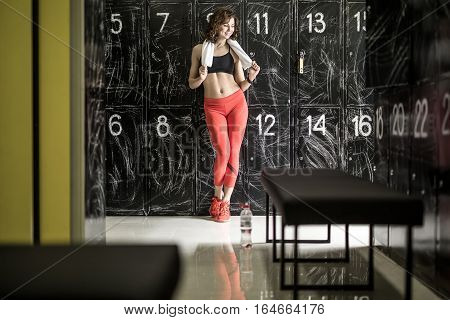 Pretty curly woman in red pants and black top stands on the background of the lockers in the locker-room in the gym. She holds a white towel and looks to the left with a smile. Horizontal.