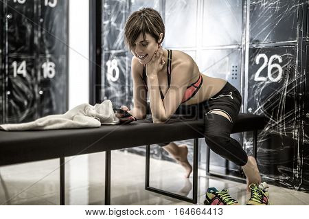 Barefoot smiling girl with a mobile phone sits on the bench in the locker-room in the gym. She wears black pants and a pink top. Woman leans on her elbows and holds left hand on the neck. Horizontal.