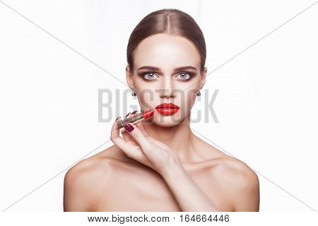 professional makeup artist applies makeup for beautiful young woman with blue eyes and light brown hair style and perfect skin. studio shot, isolated on white background.