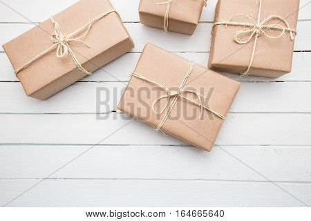 Close up Christmas style rustic brown paper package tied up with strings. White wood background.