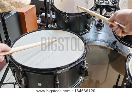 Two hands drumsticks beating on a drum, first-person view