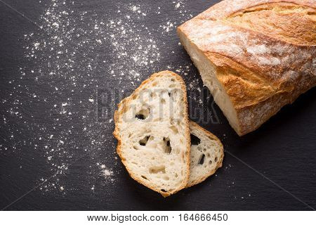 A loaf of wheat bread and slices on a slate plate