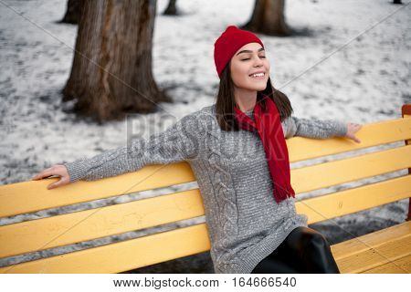 Girl in red hat and scarf is resting on bench in winter park. She is very pleased and happy and sitting on a bench.