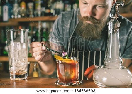 Handsome barman is making cocktail at night club. Unique man. Bartender has a mustache and stylish hairstyle, looking at camera