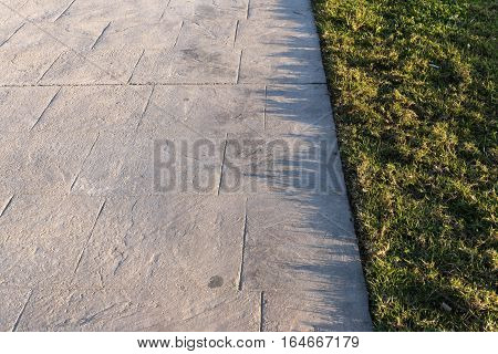 Stamped concrete pavement outdoor with an expansion joint at top, decorative appearance colors and textures of paving slate stone tile on cement design, perspective