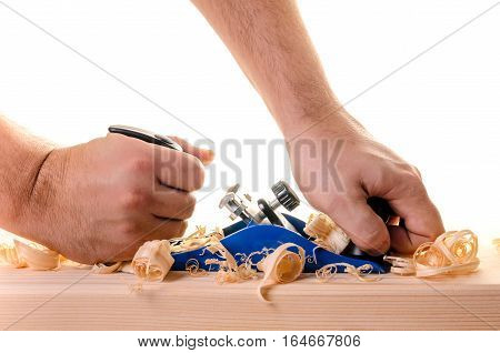 Carpenter working with planer on wooden plank