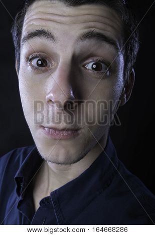 portrait of young man wearing blue shirt making silly faces against black background