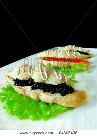 Snack for banquet consisting of croissant and black and red caviar on a plate