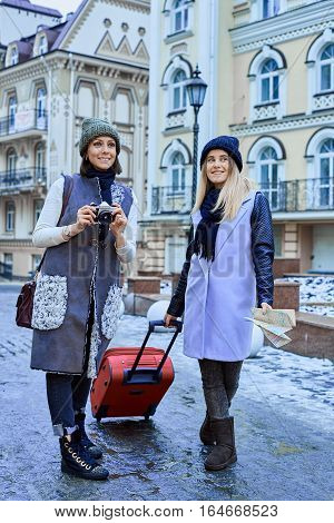 Two friends tourists are walking in old town with camera and map after arrival.