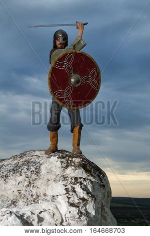 Knight on a rock with a sword against blue cloudy sky