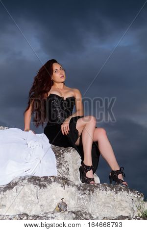 beautiful young woman in a black dress on a background of the cloudy sky
