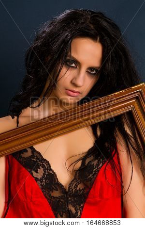 Young beautiful brunette woman in beautiful red lingerie on dark background