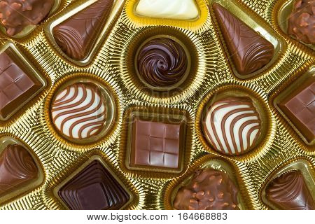 Assortment of fine chocolate candies pralines white dark and milk chocolate in golden box. Product concept for patisserie. Top View.