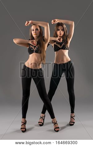 Two young long haired brunette in black leggings, high heel shoes and black bras decorated with silver rhinestones posing in studio making dance moves