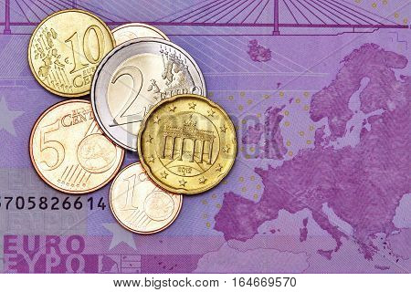 Several euro coins on a euro banknote