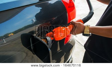 Employee is fueling into tank of the car Hand holding fuel nozzle