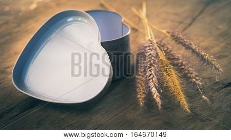 heart-shaped box with fountain grasses on a wooden board- split toning effect