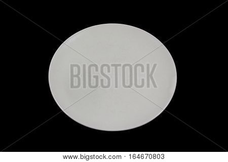 Flat off white shallow plate on black background directly from high angle