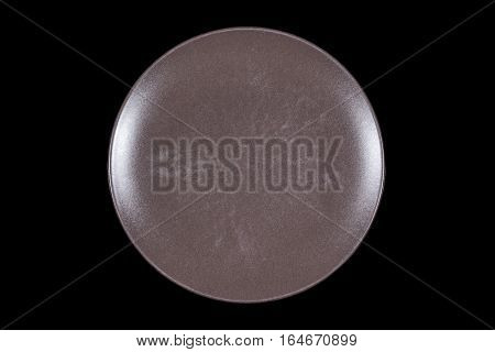 Dark brown flat shallow ceramic plate on black background directly from above