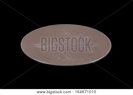 Dark brown flat shallow ceramic plate on black background directly from side