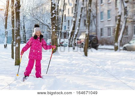 Cute little teenage girl is skiing on winter sunny day in snow park. Teen in pink sport jacket with ski poles in hands. Consequences of snowfall in urban environment