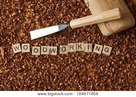 Love woodworking word writen with letters on wood chips with a chisel and a mallet