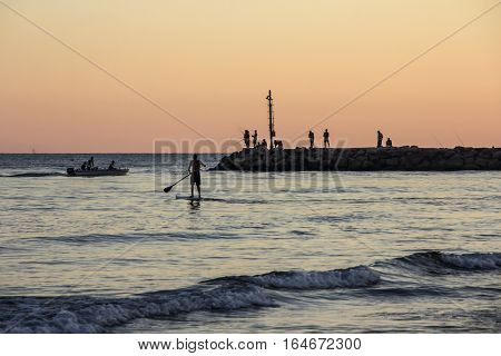 Sunset on Tyrrhenian sea, view of breakwater, SUP surfer, harbor and seacoast of Terracina, Lazio, Italy