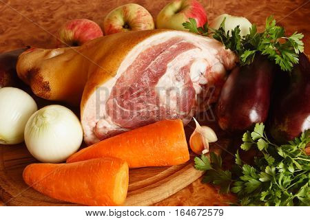 Pork meat with bone pork knuckle with vegetables on a chopping board