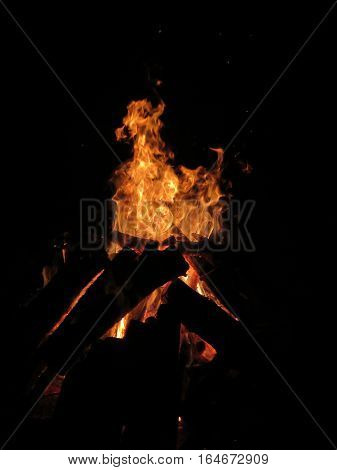 A roaring Bonfire made of stacked up logs with Bright Orange flames contrasting the Black night and Log silhouettes that surround it. For those who it interests the flames create the figure of whatever animal you choose to interpret them as. For me a Llam