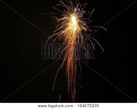 A firework rocketing into the sky and exploding, creating rich shades of yellow, orange and red against a pitch black, night sky. Taken on Bonfire night.