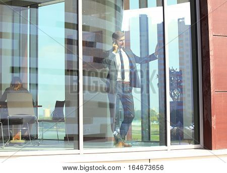 handsome young businessman in a stylish modern office space with large windows, talking on the phone and looking outside